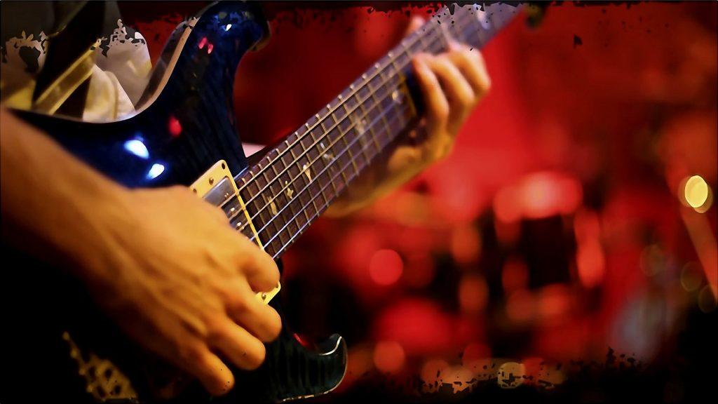 A Close-up iew of a man plays a bass guitar.