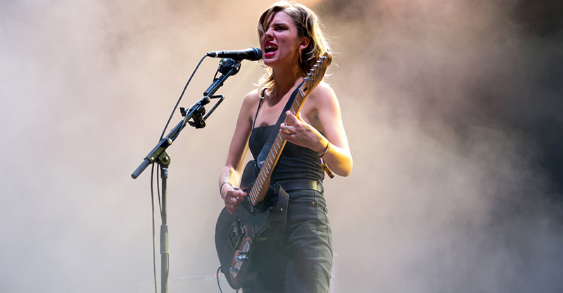 Image showing a beautiful girl with guitar performing in the stage in a smoke background.